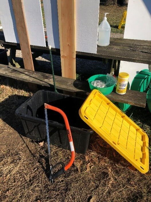 a handsaw and bucket at a tree farm